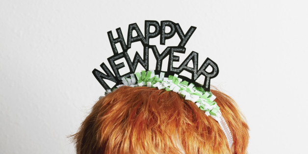 A woman wearing a party tiara with Happy New Year on it, top of head