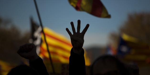 A pro Independence demonstrator gestures  - four fingers symbolizing the four bars of the Catalonian flag, during a demonstrations to show public support for the Parliament of Catalonia, in Barcelona, Spain, Sunday, Nov. 22, 2015. Prime Minister Mariano Rajoy made his first visit to the regional capital of Catalonia on Saturday following his administration's legal push to halt an effort secessionist regional parties to declare independence from Spain by 2017. (AP Photo/Emilio Morenatti)