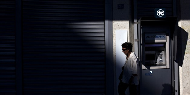 A woman walks in front of the ATM of an Alpha Bank branch in Athens on July 19, 2015. Banks are set to reopen Monday after a three-week shutdown estimated to have cost the economy some 3.0 billion euros ($3.3 billion) in market shortages and export disruption. AFP PHOTO / ANGELOS TZORTZINIS        (Photo credit should read ANGELOS TZORTZINIS/AFP/Getty Images)