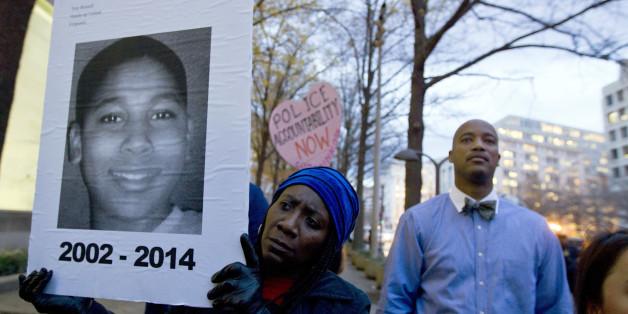 한 여성이 피해자 타미르 라이스의 사진이 인쇄된 피켓을 들고 있다. 2014. 11. 22.