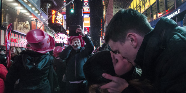 Sean Reilly and Emily Verselin share a kiss at midnight in Times Square during a New Year's Eve celebration, Thursday, Jan. 1, 2015, in New York. Thousands braved the cold to watch the annual ball drop and ring in the new year. (AP Photo/John Minchillo)