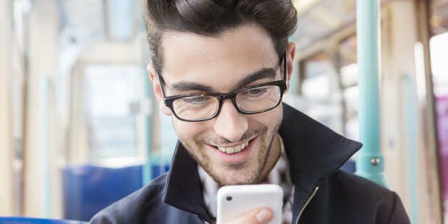 man sitting in public transport looking at phone.