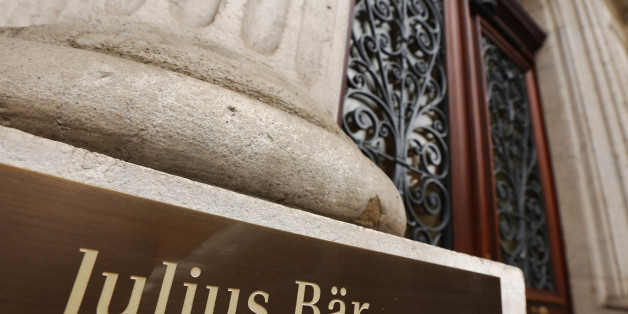 A sign sits by the entrance to Bank Julius Baer & Company Ltd. in Geneva, Switzerland, on Friday, Oct. 16, 2015. Once bastions of secrecy, 41 Swiss banks signed amnesty agreements this year with the U.S. Justice Department that required disclosing the tricks they used to help customers hide assets, naming bankers and middlemen who enabled them and detailing the flow of untaxed money. Photographer: Luke MacGregor/Bloomberg via Getty Images