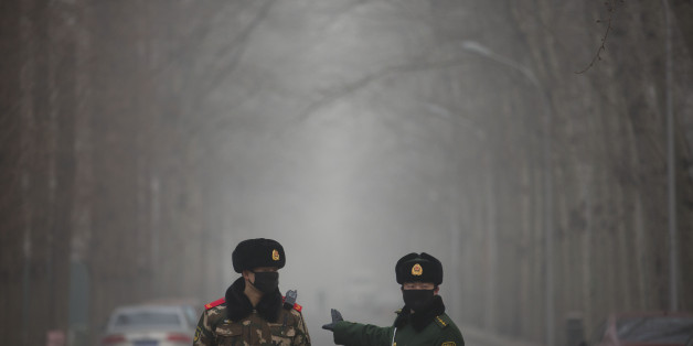Chinese paramilitary policemen stop a car from entering a blocked-off road in an embassy district in Beijing, Friday, Dec. 25, 2015. Security remained elevated in parts of Beijing on Friday, a day after the U.S. and other foreign embassies in China warned of potential threats to Westerners around the Christmas holiday. (AP Photo/Mark Schiefelbein)