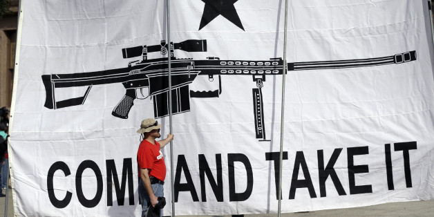 "FILE - In this Jan. 26, 2015 file photo, a demonstrator helps hold a large ""Come and Take It"" banner at a rally in support of open carry gun laws at the Capitol, in Austin, Texas. Texas, the second-most populous state, is joining 44 other states in allowing at least some firearm owners to carry handguns openly in public places. Under the Texas law, guns can be carried by those with licenses and only in holsters. (AP Photo/Eric Gay, File)"