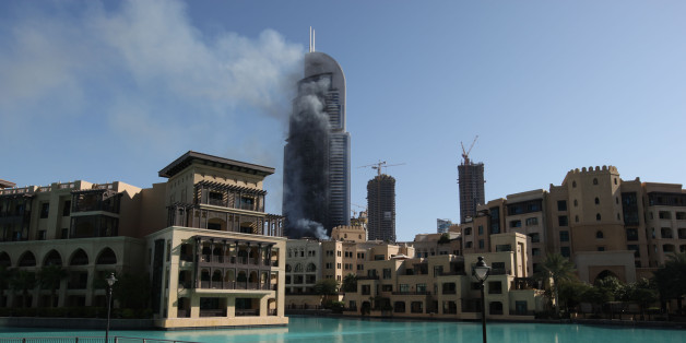 Smoke billows from the Address Downtown skyscraper in Dubai, United Arab Emirates on Friday, Jan. 1, 2016. The blaze began Thursday night before Dubai's annual New Year's Eve fireworks show at the Burj Khalifa, the world's tallest building which sits nearby. (AP Photo/Jon Gambrell)