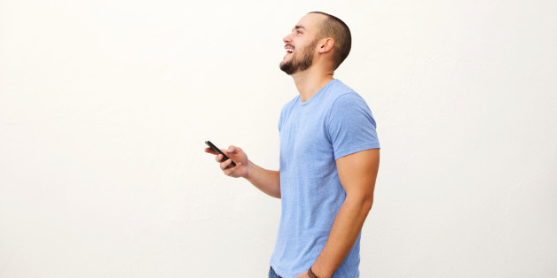 Cheerful young man walking with mobile phone against white background