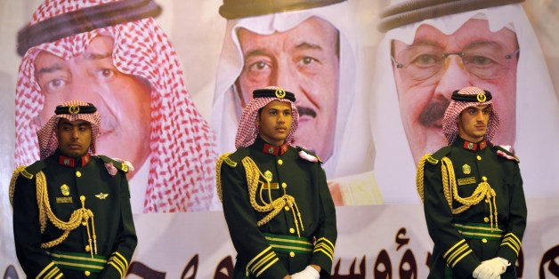 FILE - In this Feb. 18, 2014 file photo, Saudi royal guards stand on duty in front of portraits of King Abdullah bin Abdulaziz, right, then Crown Prince Salman bin Abdulaziz, center, and Muqrin bin Abdulaziz during a culture festival in Riyadh, Saudi Arabia. WikiLeaks is in the process of publishing more than 500,000 Saudi diplomatic documents to the Internet, the transparency website said Friday, June 19, 2015. If genuine, the documents would offer a rare glimpse into the inner workings of the