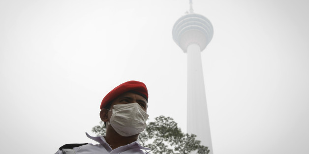 A security man stands guard in front of the Kuala Lumpur Tower shrouded by haze in Kuala Lumpur, Malaysia Monday, Sept. 14, 2015. On Monday unhealthy API (Air Pollutant Index) readings were recorded at 30 locations nationwide as persistent haze from Indonesian forest fires worsened. (AP Photo/Joshua Paul)