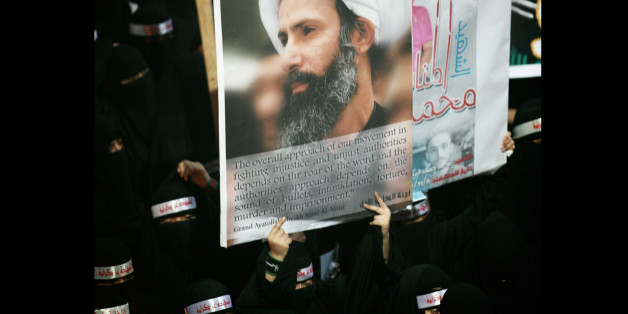 FILE - In this Sunday, Sept. 30, 2012 file photo, a Saudi anti-government protester carries a poster with the image of jailed Shiite cleric Sheik Nimr al-Nimr during the funeral of three Shiite Muslims allegedly killed by Saudi security forces in the eastern town of al-Awamiya, Saudi Arabia. A court in Saudi Arabia has postponed issuing a verdict in a sensitive case against a popular Shiite cleric who faces charges that carry the death sentence. Al-Nimr's brother Mohammed al-Nimr told The Associated Press that the verdict was delayed until Oct. 21. (AP Photo, File)