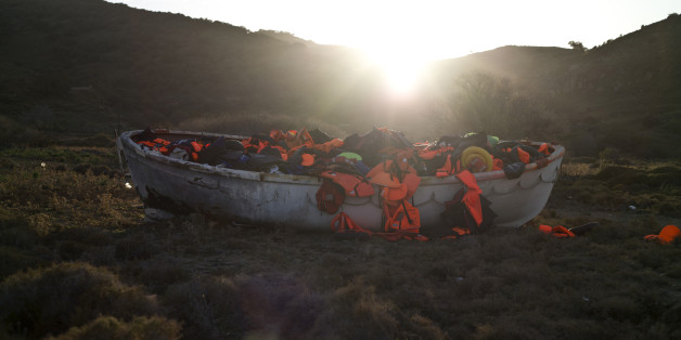 A wooden boat full of life jackets used by refugees and migrants to cross the Aegean sea from the Turkish coast remains on the shore of the Greek island of Lesbos, Monday, Nov. 23 , 2015.  Hundreds of migrants have been stranded at the Greek-Macedonian border for days, after Macedonia and other Balkan countries toughened criteria for crossings. (AP Photo/Muhammed Muheisen)