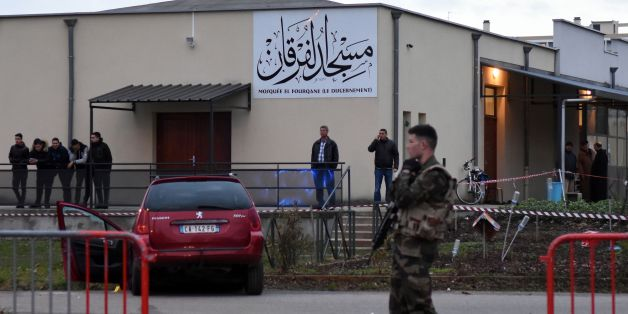 French police officers and soldiers stand near a red car in front of the mosque of Valence, southeastern France, on January 1, 2016, after a soldier guarding the mosque shot and wounded a driver who rammed him with a car.                                 Police said the driver deliberately drove his Peugeot into the soldier in the southeastern city of Valence. The impact of the car left the soldier with injuries to his knee and shin. Police said the driver's motive remained unclear. / AFP / PATRI