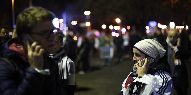 HANOVER, GERMANY - NOVEMBER 17:  People speak on their mobile phone shortly after the match between Germany and the Netherlands was cancelled following a bomb alert at the HDI-Arena on November 17, 2015 in Hanover, Germany. The Match was cancelled after unoffical sources said there was a bomb inside a car at the parking area at the front gate. Special Forces from other cities are expected to arrive shortly at the scene. The German Federal Police raised the number of heavily armed police officers inside the main train station and airport at Hanover and at the HDI-Arena, in order to increase security  after the attacks in Paris last week. German chancellor Angela Merkel and members of the German Federal cabinet were expected to be among the guests at the match.  (Photo by Alexander Koerner/Getty Images)