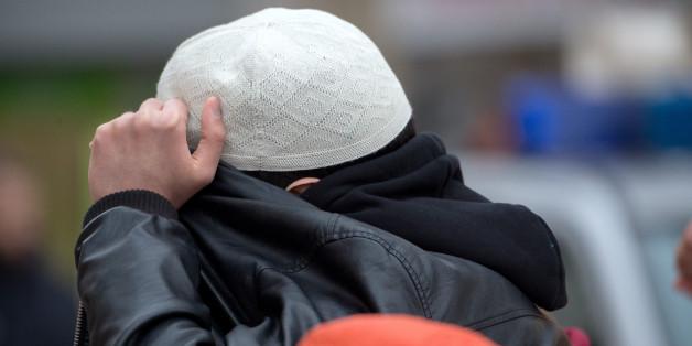 """Mit seiner Jacke verdeckt ein Mann aus dem Umfeld der Koran-Verteilaktion """"Lies"""" am 31.01.2015 in Frankfurt am Main sein Gesicht (Archivbild)"""