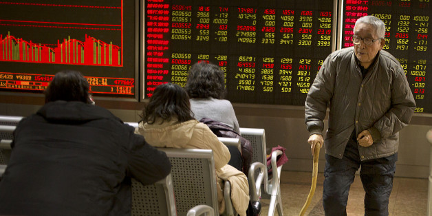 A Chinese investor walks through a brokerage house in Beijing, Friday, Dec. 4, 2015. Asian stocks sank Friday, extending a sell-off in world markets after Europe's central bank unveiled plans to stimulate the continent's ailing economy that fell short of investor expectations. (AP Photo/Mark Schiefelbein)