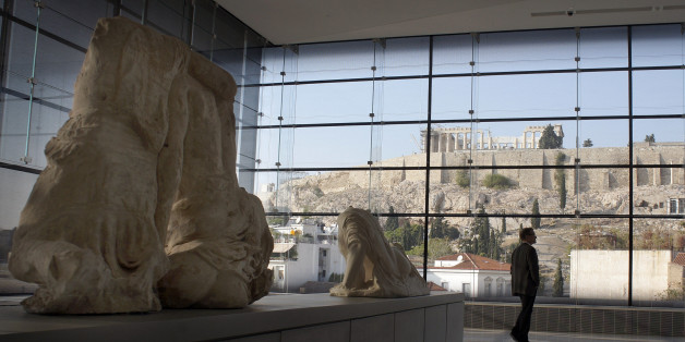 ATHENS, GREECE - OCTOBER 14:  Visitors to Athens' Acropolis Museum look at the frieze of the Temple of Parthenon on October 14, 2014 in Athens, Greece.  Lawyers Geoffrey Robertson and Amal Alamuddin are on a four-day visit to meet with government officials and advise on the return of the Parthenon Marbles, also known as the Elgin Marbles. Alamuddin's husband, actor George Clooney, campaigned for the Marbles' return when promoting his film 'The Monuments Men'.  (Photo by Milos Bicanski/Getty Images)