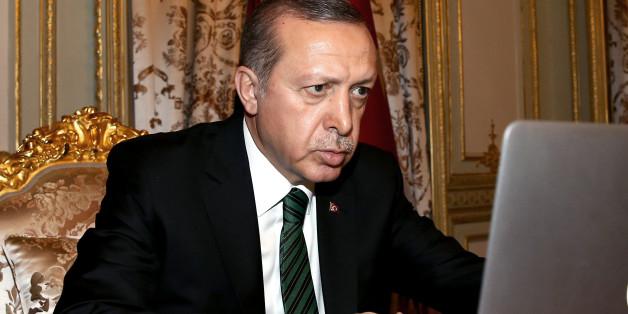 Turkey's President Recep Tayyip Erdogan checks to vote for photos produced in 2015 by semi-offcial Anadolu agency photographers, in Istanbul, late Friday, Dec. 25, 2015. (Basin Bulbul, Presidential Press Service Pool via AP)