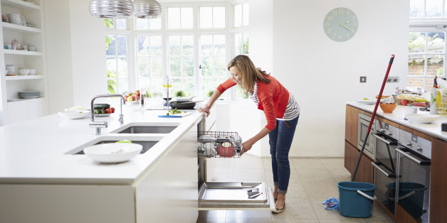 Woman Bending Down Loading Plates Into Dishwasher