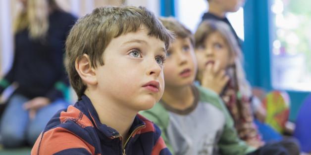 Ein Kind hört dem Lehrer in einem Klassenzimmer zu.