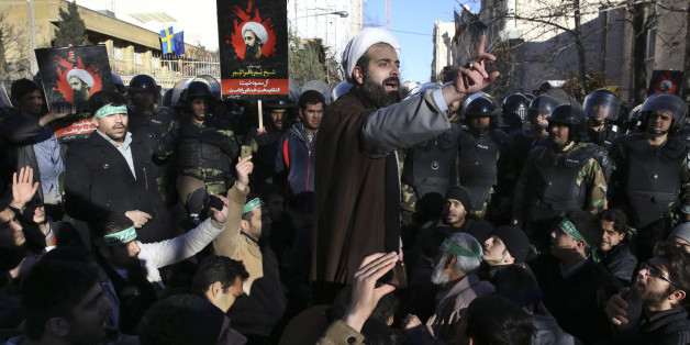 Surrounded by policemen, a Muslim cleric addresses a crowd during a demonstration to denounce the execution of Saudi Shiite Sheikh Nimr al-Nimr, seen in poster, in front of the Saudi embassy in Tehran, Iran, Sunday, Jan. 3, 2016. Saudi Arabia announced the execution of al-Nimr on Saturday along with 46 others. Al-Nimr was a central figure in protests by Saudi Arabia's Shiite minority until his arrest in 2012, and his execution drew condemnation from Shiites across the region. (AP Photo/Vahid Salemi)