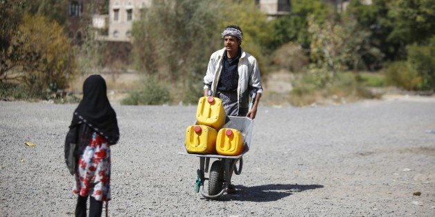 A man pushes a cart loaded buckets to fill with water from a public tap amid an acute shortage of water, in the old city of Sanaa, Yemen, Wednesday, Nov. 25, 2015. (AP Photo/Hani Mohammed)