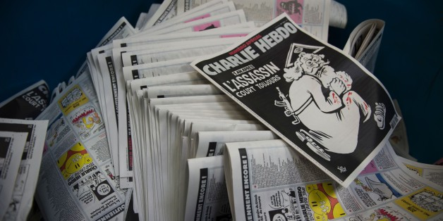 A picture taken on January 4, 2016 at a printing house near Paris shows the cover of the latest edition of the French Satirical magazine Charlie Hebdo bearing a headline which translates as 'One year on: The assassin still at large' in an edition to mark the first anniversary of the terror attack which targetted the magazines offices in Paris on January 7, 2015.