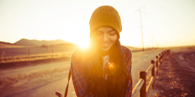 young woman sitting on fence post at sunset