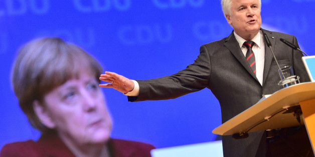 KARLSRUHE, GERMANY - DECEMBER 15:  Horst Seehofer, head of Bavarian Christian Democrats (CSU) and Governeur of Bavaria speaks while the face of German Chancellor and Chairwoman of the German Christian Democrats (CDU) Angela Merkel is seen on the screen behind him at the annual CDU federal congress on December 15, 2015 in Karlsruhe, Germany. The CDU is meeting following a dramatic year in which Germany admitted approximately one million migrants and refugees under an open-door policy spearheaded