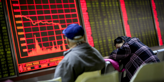 A woman takes a nap as a man looks at an electronic board displaying stock prices at a brokerage house in Beijing, Monday, Jan. 4, 2016. Shanghai's stock index plunged nearly 7 percent on Monday, sparking a halt in trading of Chinese shares, after weak manufacturing data and Middle East tensions weighed on Asian markets. (AP Photo/Andy Wong)