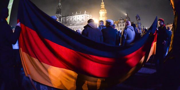 Pegida-Demonstranten haben am 19.10.2015 in Dresden eine Deutschlandfahne ausgebreitet. Ähnlich wie bei den Patriotischen Europäern gibt es auch bei den Reichsbürgern Sympathisanten, die der rechten Szene einzuordnen sind (Archivbild)