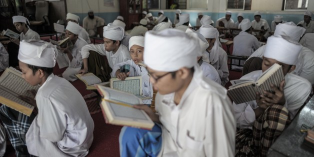 A Malaysian religious student (C) looks on as others read and memorise the Koran at a seminary during the Muslim holy fasting month of Ramadan in Hulu Langat, near Kuala Lumpur on June 22, 2015. Islam's holy month of Ramadan is celebrated by Muslims worldwide marked by fasting, abstaining from foods, sex and smoking from dawn to dusk for soul cleansing and strengthening the spiritual bond between them and the Almighty. AFP PHOTO / MOHD RASFAN        (Photo credit should read MOHD RASFAN/AFP/Gett