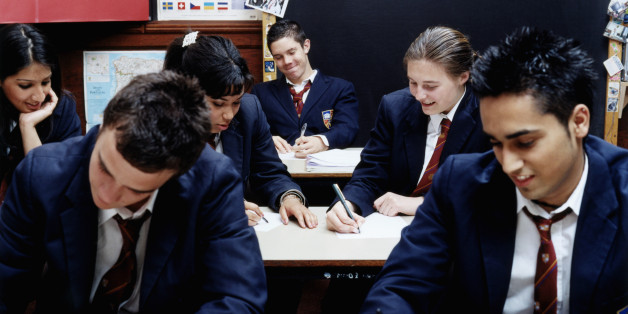 Teenage schoolchildren (14-16) writing in classroom