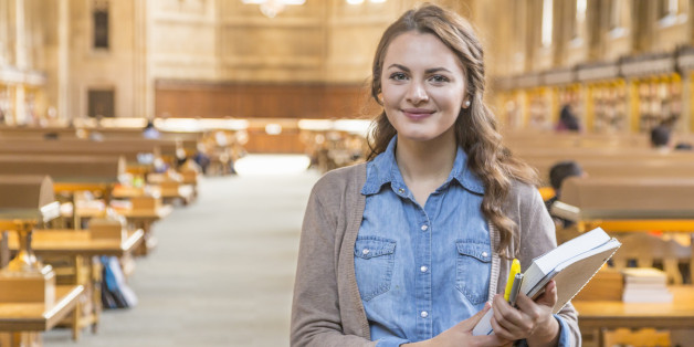 A smiling college student with books in library
