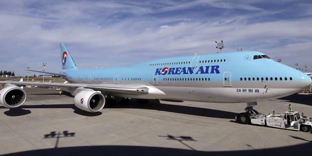As another plane flies overhead, a Boeing 747-8 Intercontinental jet is moved into position for a delivery ceremony to Korean Air, Tuesday, Aug. 25, 2015, in Everett, Wash. The jet is the first of 10 of the passenger airplanes the carrier has on order with Boeing. With the delivery, Korean Air becomes the first airline to operate both passenger and freighter versions of the 747-8. (AP Photo/Elaine Thompson)