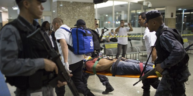 Police and rescue workers carry a fellow officer on a stretcher during a security drill that simulated a store robbery at the Novo Rio bus station in Rio de Janeiro, Brazil, Thursday, Oct. 1, 2015. Police also practiced handling a bus hijacking that involved hostage negotiation. (AP Photo/Leo Correa)