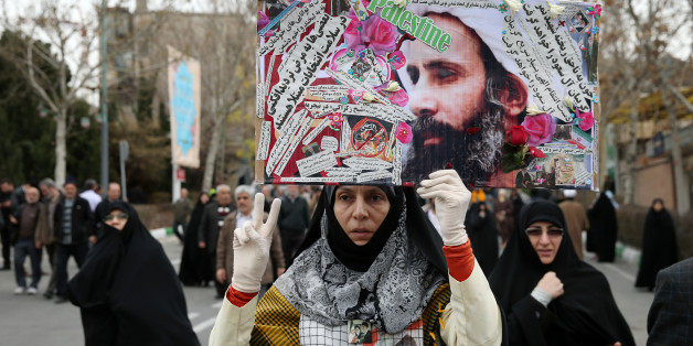 "An Iranian worshipper holds up a poster showing Sheikh Nimr al-Nimr, a prominent opposition Saudi Shiite cleric who was executed by Saudi Arabia, as she shows victory sign while attending an anti-Saudi protest rally after the Friday prayers in Tehran, Iran, Friday, Jan. 8, 2016. Thousands of worshippers who took part in Friday prayers in Tehran joined the rally, carrying pictures of al-Nimr and chanting ""Death to Al Saud,"" referencing the kingdom's royal family. Iranian state media reported simi"