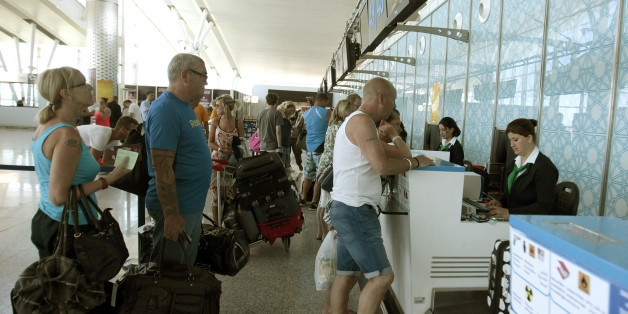 Tourists line up at a boarding desk as the leave Sousse, Tunisia, after the attack, Saturday June 27, 2015 at the Nfidha airport near Sousse. Tunisia's prime minister announced on Saturday a string of new security measures including closing renegade mosques and calling up army reservists as thousands of tourists left the North African country in wake of its worst terrorist attack ever. (AP Photo/Salah Rhim)
