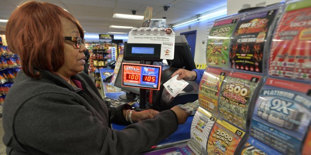 In this Oct. 23, 2015 photo, Vera Washington of Chicago, buys lotto tickets at the K&D Marathon station in Hammond, Ind. With Illinois delaying payouts over $600 because of its budget mess, neighboring states are salivating at the chance to boost sales. Businesses near borders, particularly in Indiana, Kentucky and Iowa, say they've already noticed a difference. The Lottery problems stemming from Illinois' budget impasse have led to a lawsuit and come amid questions about Illinois reve