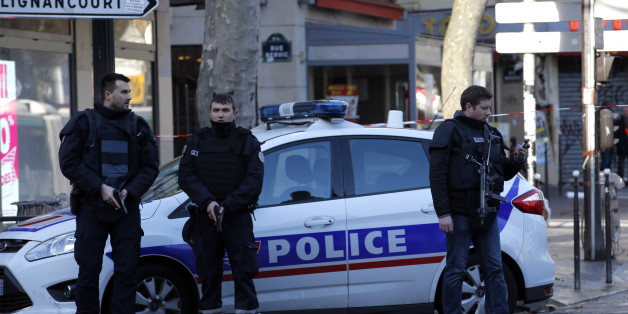 A police officer guards the police station, seen in background, after officers shot and killed a knife-wielding man wearing a fake explosives vest,  in Paris, Thursday, Jan. 7, 2016. Officers shot and killed a knife-wielding man wearing a fake explosive vest at a police station in northern Paris on Thursday, French officials said, a year to the day after an attack on the French satirical newspaper Charlie Hebdo launched a bloody year in the French capital. (AP Photo/Michel Euler)