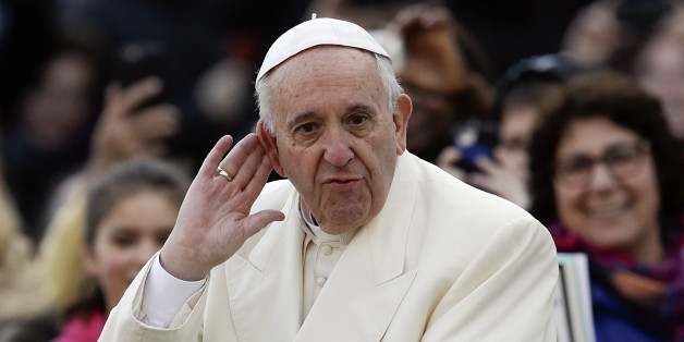 Pope Francis puts his hand to his ear to listen to a musical band playing as he arrives on his popemobile in St. Peter's Square for the weekly general audience, at the Vatican, Wednesday, Dec. 9, 2015. (AP Photo/Gregorio Borgia)