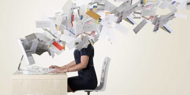 Businesswoman's head covered with flying paperwork