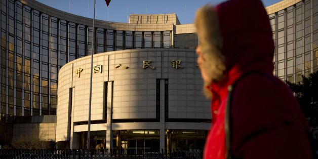 In this Friday, Jan. 8, 2016 photo, a woman walks past China's central bank, the People's Bank of China, in Beijing. Stock market and currency turmoil has battered Chinese leaders' reputation as shrewd economic managers and fed doubts about their ability and willingness to push more wrenching reforms. (AP Photo/Mark Schiefelbein)