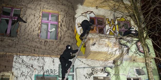 Zwei Polizisten versuchen über eine Leiter in das Haus in der Rigaer Straße zu gelangen