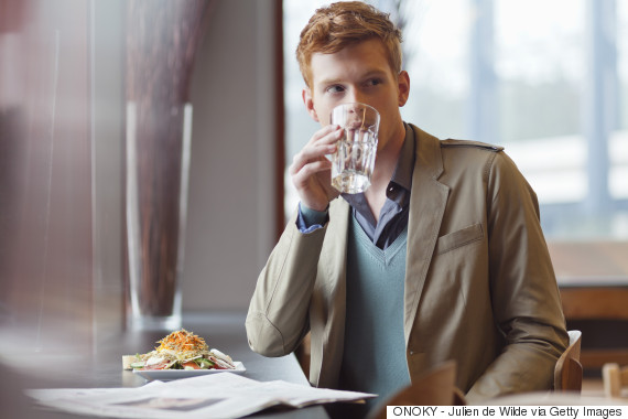 man drinking water in restaurant