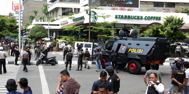 Police officers stand guard outside a Starbucks cafe near where an explosion went off in Jakarta, Indonesia Thursday, Jan. 14, 2016. Attackers set off explosions at a Starbucks cafe in a bustling shopping area of downtown Jakarta and waged gun-battles with police Thursday, leaving bodies in the streets as office workers watched in terror from high-rise windows. (AP Photo/Achmad Ibrahim)