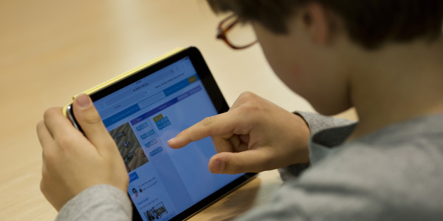 A kid learns how to build a video game using code on an Apple Inc. iPad Mini during the Hour of Code workshop at an Apple store in New York, U.S., on Thursday, Dec. 10, 2015. Hour of Code, a free one-hour introduction to the basics of computer programming, is a special event for kids ages six and up hosted by Apple Inc. in conjunction with Computer Science Education Week. Photographer: Victor J. Blue/Bloomberg via Getty Images