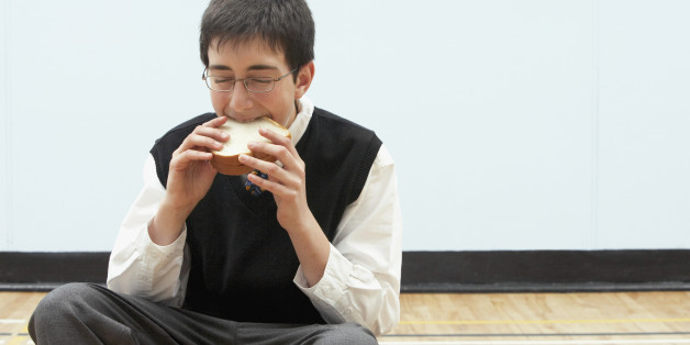 Boy (11-13) eating sandwich in school gymnasium, eyes closed