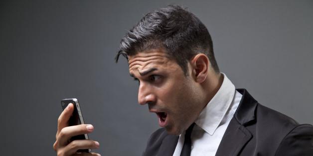 46c070cbaaf Hombre vestido de traje y corbata, mirando un mensaje en el móvil con cara  de