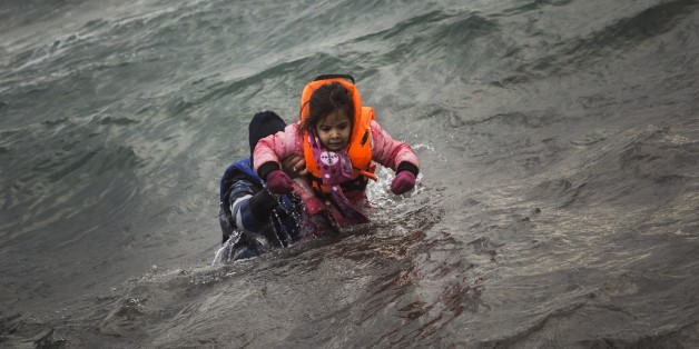 A man carries a child as they try to reach a shore after falling into the sea while disembarking from a dinghy on which they crossed a part of the Aegean sea with other refugees and migrants, from Turkey to the Greek island of Lesbos, on Sunday, Jan. 3, 2016. More than a million people reached Europe in 2015 in the continent's largest refugee influx since the end of World War II. Nearly 3,800 people are estimated to have drowned in the Mediterranean last year, making the journey to Greece or Ita