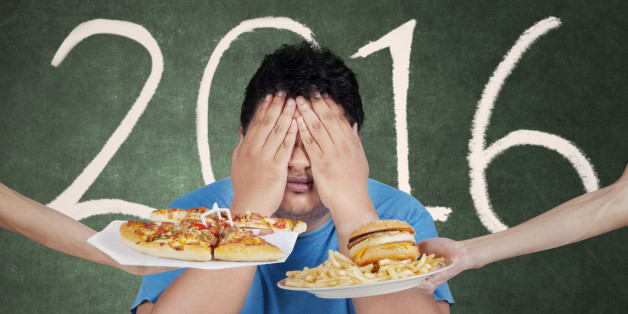 Portrait of overweight person rejects fast food and close his eye with numbers 2016 on the blackboard